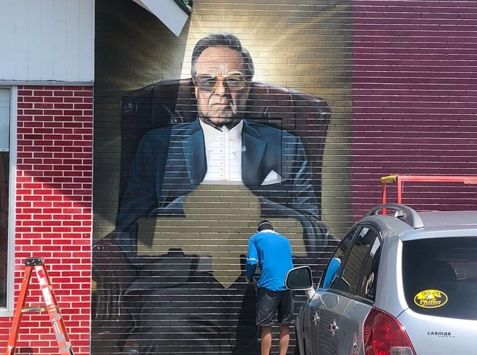 An artist named Douglas Panzone is painting a mural in Avondale